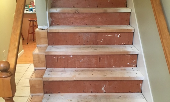 <p>Originally these stairs were carpeted with faux maple reveals on the left. The carpet, tack strip, and spindles were removed.</p>